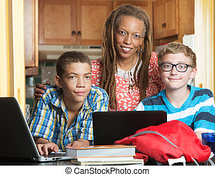 Smiling mother with son and his friend doing homework in kitchen