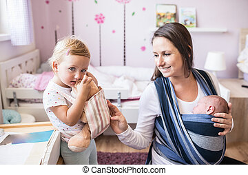 Mother with son in sling and daughter carrying teddy bear -...