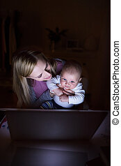 Mother with son in the arms, working on laptop