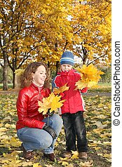 mother with son in the park in autumn with yello leaves
