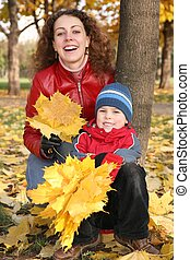 mother with son in the park in autumn with yellow leaves 2