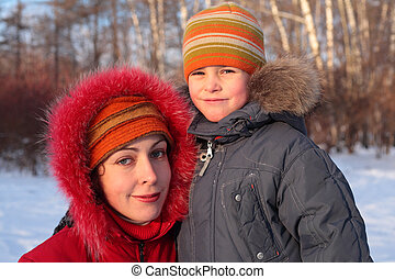 Mother with son in wood in winter