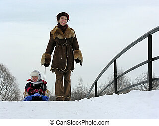mother with son on sled.