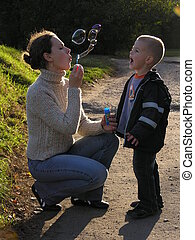 mother with son on sundown with soapy bubble