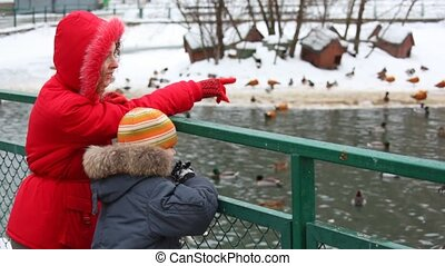 mother with son on winter pond