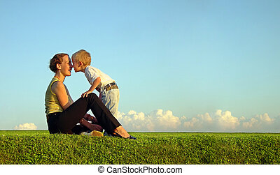 mother with son on sundown kiss by nose. long.