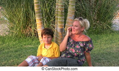 Mother with son, talking on phone