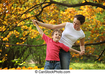 Mother with son to keep for hands in garden in spring