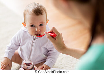 mother with spoon feeding little baby at home