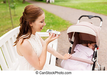 mother with stroller and smartphone at summer park