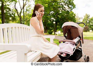 mother with stroller calling on smartphone at park
