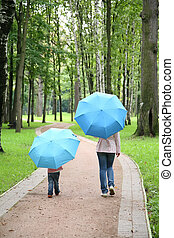 mother with the child under the umbrellas in the park