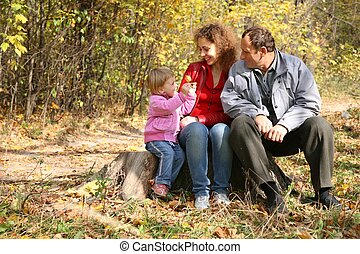 mother with the daughter and the grandfather in the park in autumn