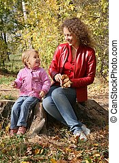 mother with the daughter sits in the park in autumn