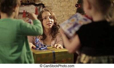 Mother with the gift talking with her children