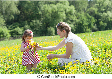 Mother with the small daughter play on a glade with dandelions