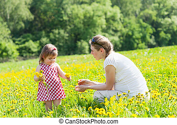 Mother with the small daughter play on a glade with...
