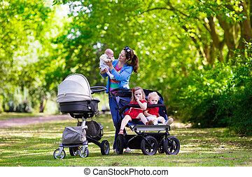 Mother with three children in buggy and stroller