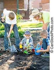 Mother with three children sons planting a tree and watering it together in garden