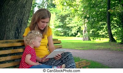 Mother with toddler daughter girl using tablet computer sit on bench in park