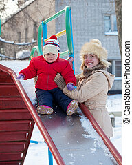 mother with toddler on slide in winter