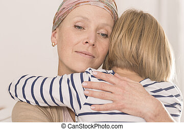 Mother with tumor hugging child