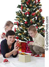 Mother with two children decorating Christmas tree