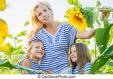 Mother with two children in sunflower field