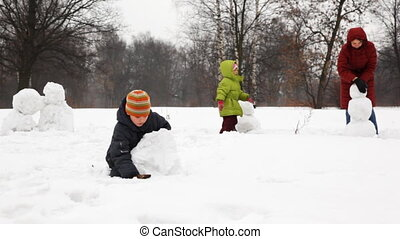 mother with two children make snowman in winter