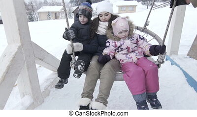 Mother with two children on large swing in winter, slowmotion