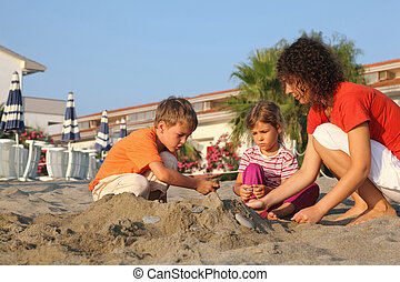Mother with two children sits on  beach in  day-time and build  hill from sand