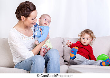 Mother with two children sitting on a couch