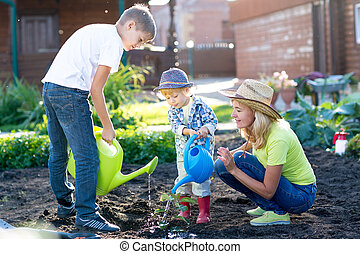Mother with two children sons planting a tree and watering it together in garden