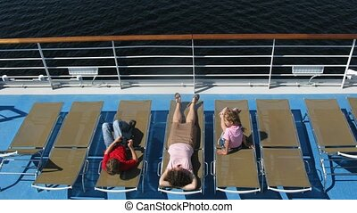Mother with two children sunbathing and playing games on sunbed on ship deck