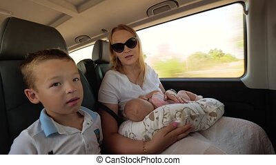 Mother with two children traveling by car