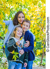 Mother with two children under autumn yellow tree smiling