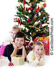 Mother with two children under Christmas tree
