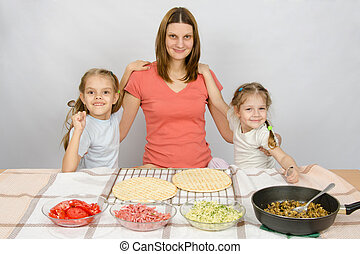 Mother with two daughters at the kitchen table are going to cook a pizza and a fun look into the frame