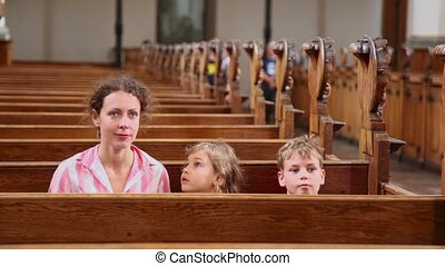 Mother with two her kids sit at bench in cathedral