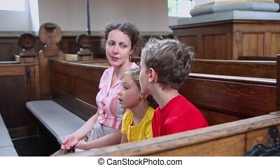 Mother with two her kids sit at bench in church