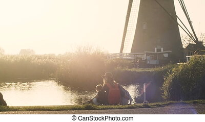 Mother with two kids near small lake at sunset. Peaceful view of Caucasian family together on a pier. 4K back view.