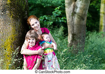Mother with two kids on a walk in the woods
