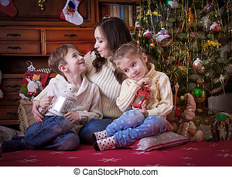 Mother with two kids under Christmas with lantern