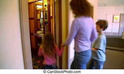 Mother with two kids walk in elevator, then doors closes