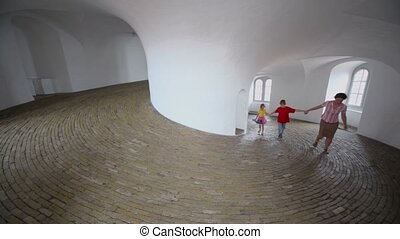 Mother with two kids walk in spiral corridor with paved floor