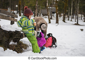 Mother with two toddler kids outside in a snowy landscape