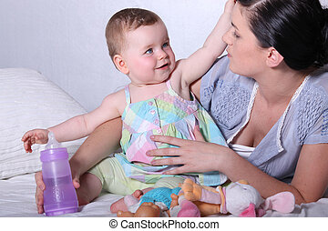 Mother with young baby and bottle on bed