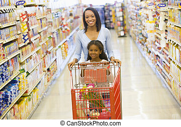 Mother with young daughter shopping at the grocery store.