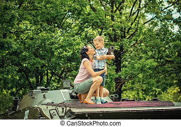 Mother with young son explore vintage military vehicles. family values on the background of a military tank