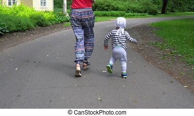 Mother Woman and Her Little son boy legs running on asphalt footpath